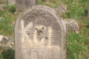The tombstone of Avraham Gershon Spszinski (d. 1908) vandalized by bullet holes and graffiti.